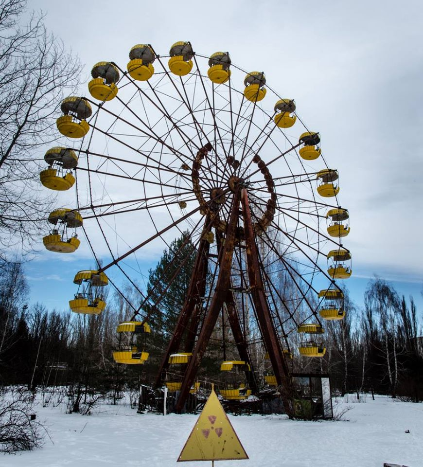 "Image of the bright yellow (now rusting) ferris wheel with a ""Caution radiation"" sign in front of it"