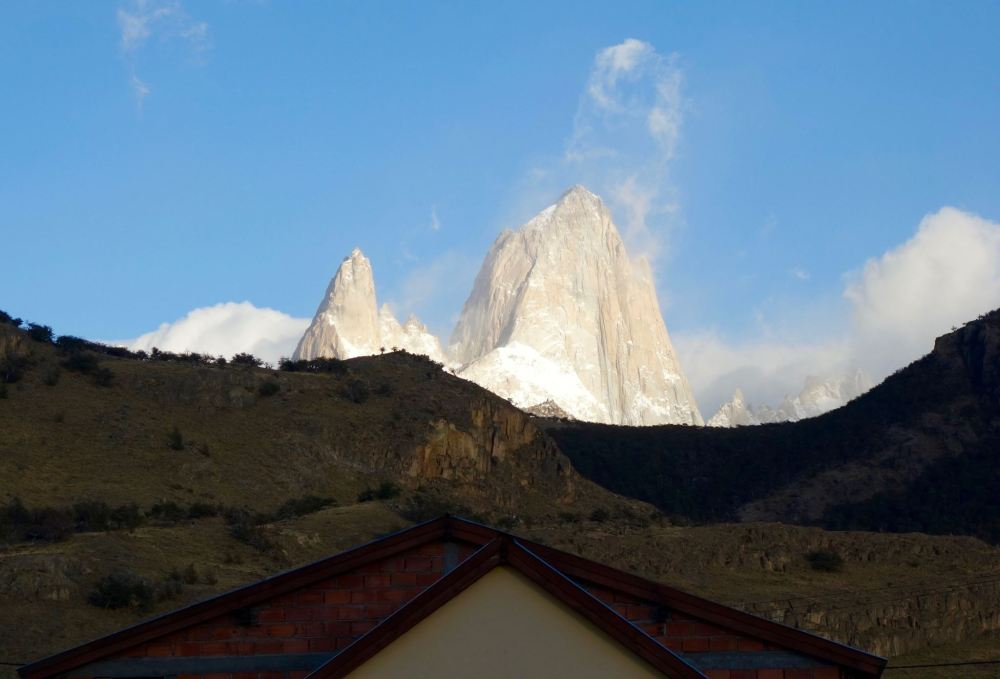 Photo of the towering peak of Fitz Roy peaking our from behind the closer hills.
