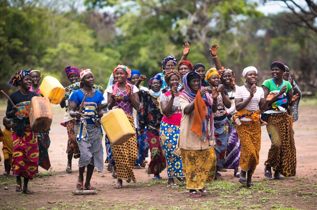 Image of ladies cheering using oil drums to make noise, all colourfully dressed and smiling
