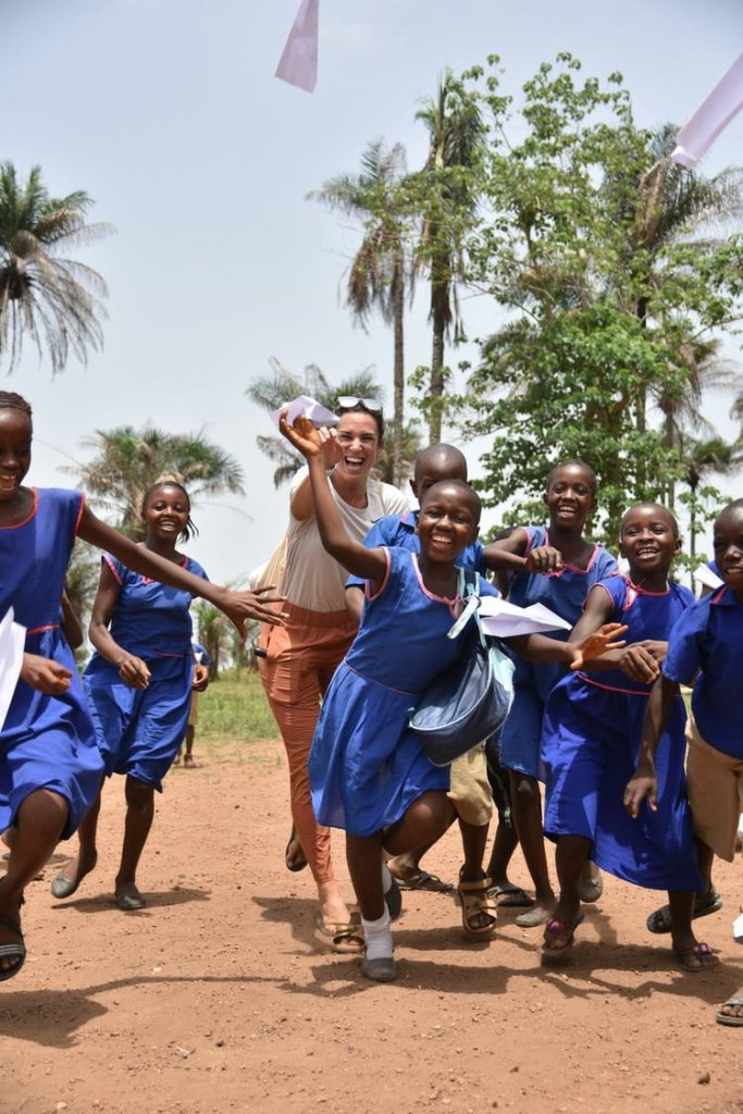 Image of school girls in uniform laughing and running after a paper airoplane