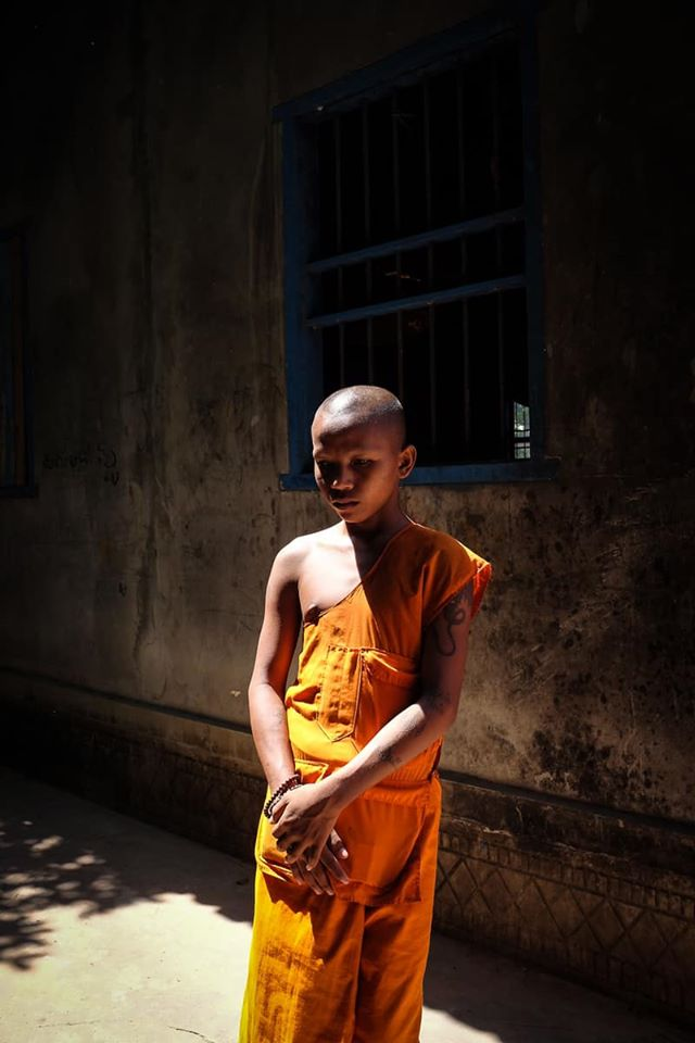 A photo of a young monk in his vibrant orange robes posing for a photo