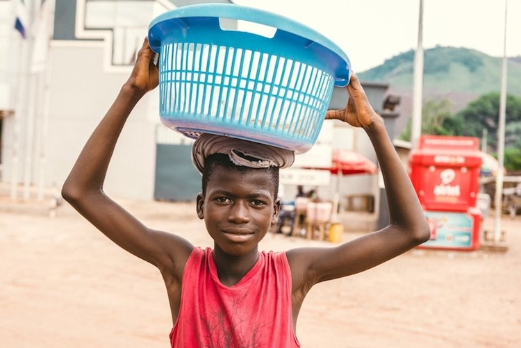 Photo of a young boy holding a washing basket it on his head as he goes about his daily routine