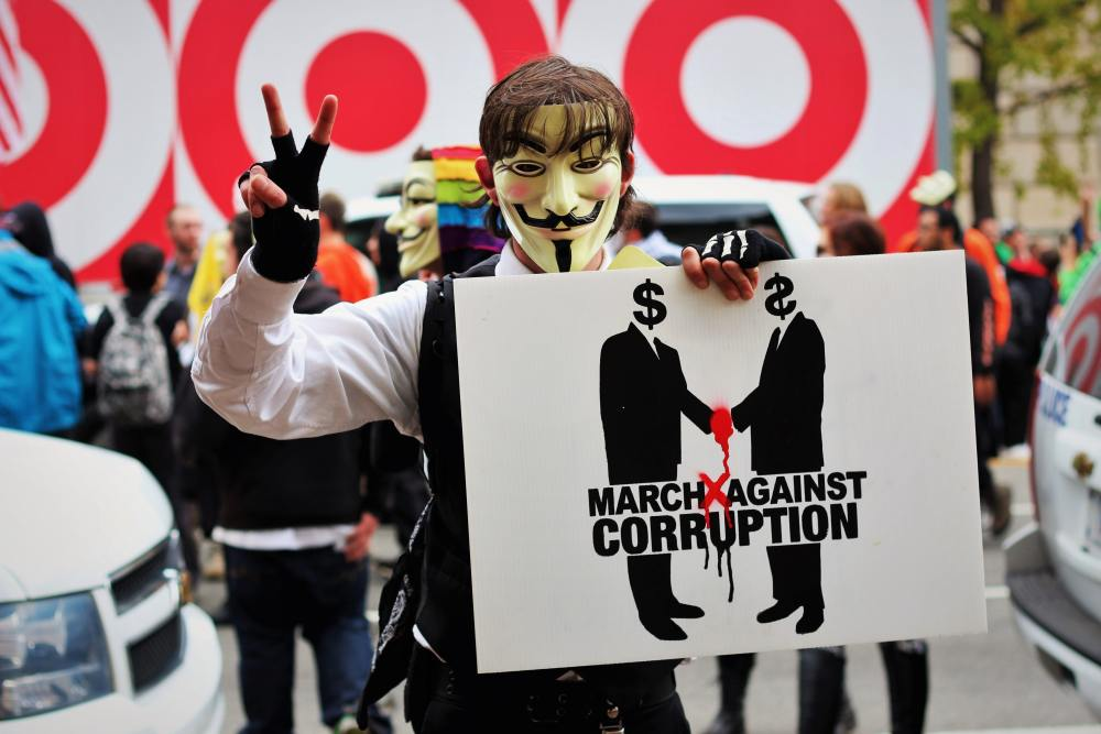 Photo of a man in a mask holding up a sign asking for people to march against corruption