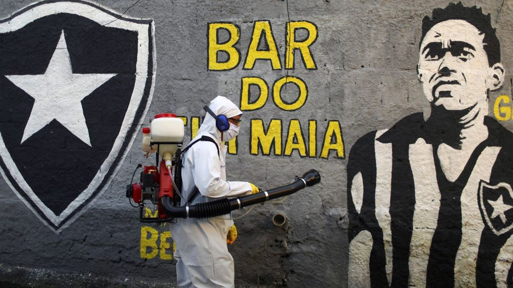 Image of man in a full suit disinfecting the streets of Rio.