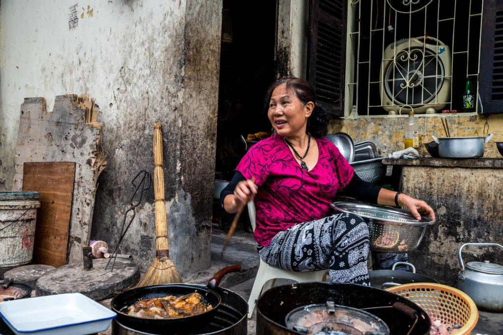 One of the top things to do in the Hanoi Old Quarter is watch life go by, in this case, a lady cooking on the pavement outside her house