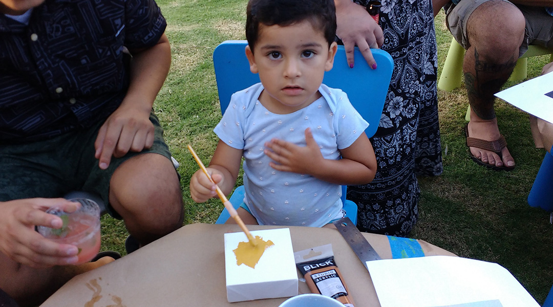 photo of a child painting on a small canvas