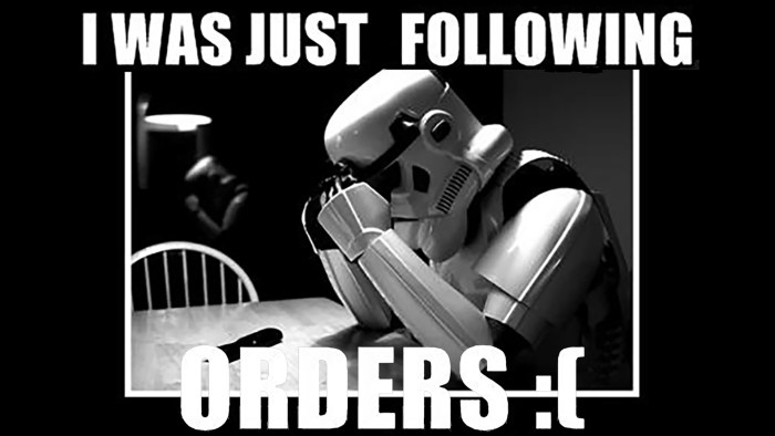 """A Star Wars Storm Trooper hunched over a table with the caption """"I was just following orders"""""""