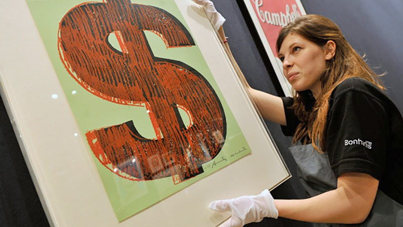 Image of an Andy Warhol dollar sign screen print in a frame being handled by a preparator in a black, Bohnam's London, t-shirt