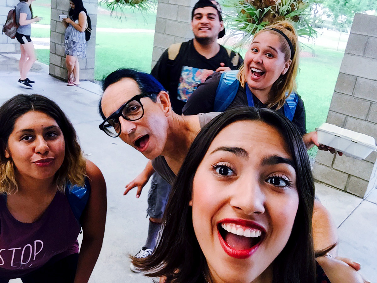 5 of us standing playfully and with big smiles in the SOA gallery courtyard as Raquel Salazar takes a group selfe of us