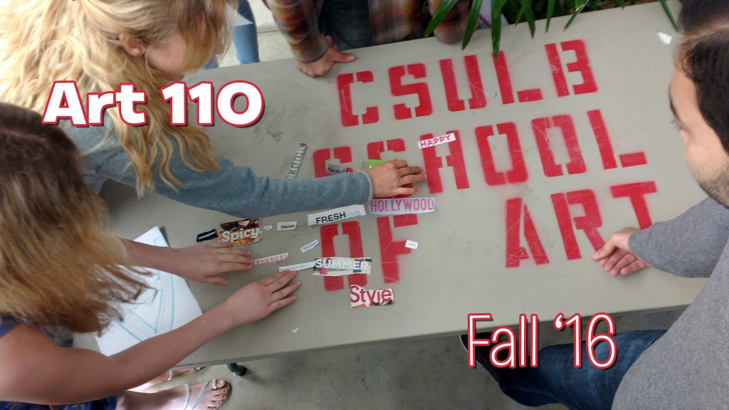 """Students working over a table that has painted on its surface """"CSULB School of Art"""""""
