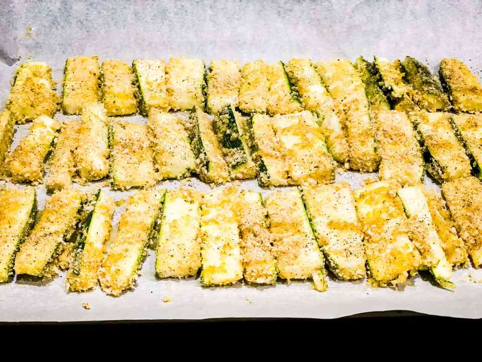 Step 3 of oven baked zucchini fries - dip the zucchini in the egg wash and then into the breadcrumbs