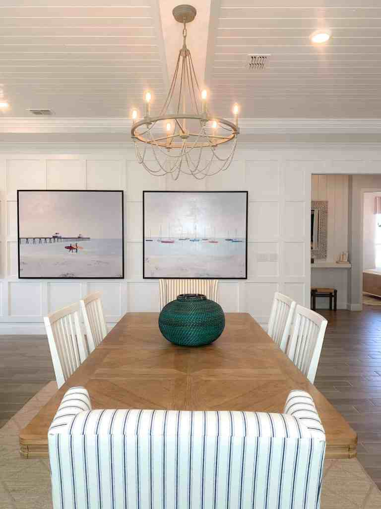 Herringbone patter dining room table.  Upholstered dining chairs.  Rope chandelier above the dining table.  Sailboat canvas art wall.