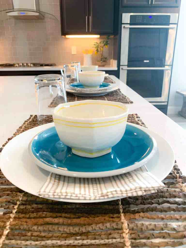 Bar top at kitchen island with rattan placemats and fun blue and yellow place settings
