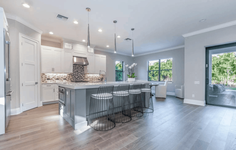 Beautiful open kitchen with white cabinets and light blue island with white countertops