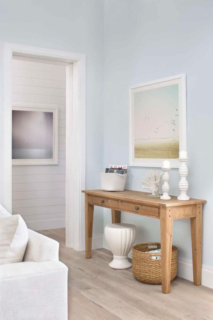 Simple Coastal Console Table Style - Wicker Basket and Neutral Beach Framed Art - Coastal Calm Home Design With Amazing Relaxed Beach Décor Ideas