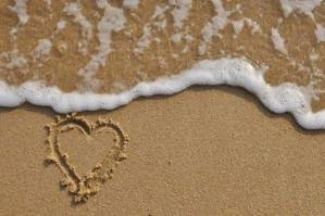 Heart drawn in the sand with foamy sea water approaching