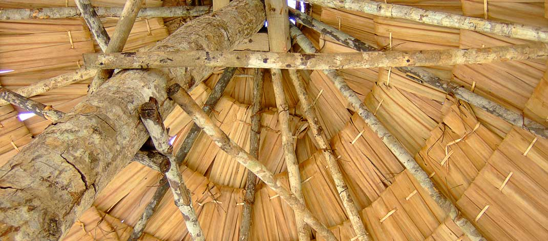 Sun umbrella made from natural materials such as wood and straw.