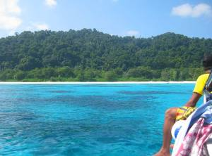 Boat in clear blue water with young tourist approaching tropical island Koh Tachai in the Andaman Sea