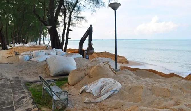 Man-made beaches in Khao Lak Thailand with sandbags and heavy machinery constructing the beach
