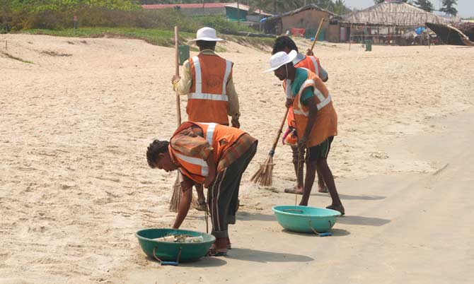 Workers in Goa groom a beach and remove beach garbage to keep the beach tidy and attractive