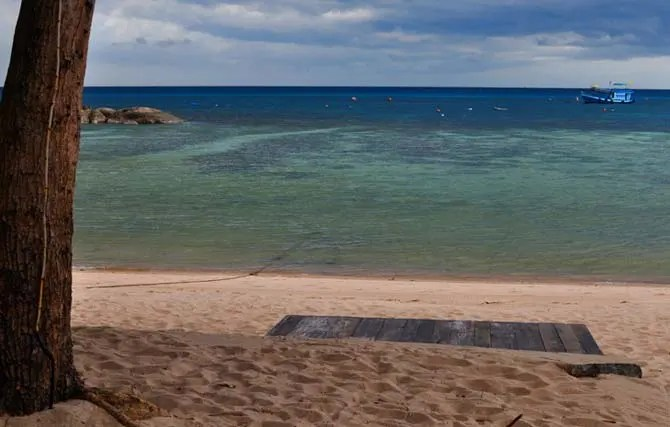 Artificial beach platform on the shore of Koh Tao with the blue sea and a boat in the background