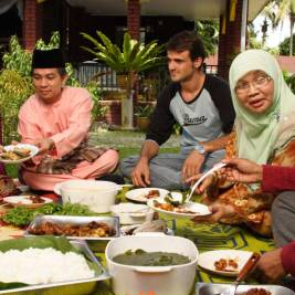 Homestay experience in Malaysia with tourists eating local Malaysian cuisine with their local homestay hosts. Homestay accommodation is one of many simple tips for sustainable travel.
