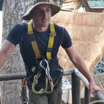 zipline instructor with rope, harness, and carabiners