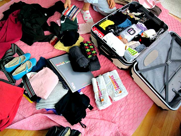 Open suitcase with clothes and travel items lying around