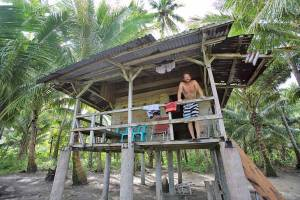 Man standing on the balcony of a charming beach hut on stilts at Walo Beach, North-West Nias, Indonesia
