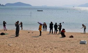 Tourists in different poses taking beach selfies and photos at Repulse Bay, Hong Kong