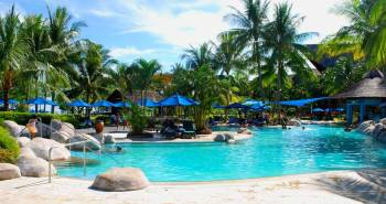 All-Inclusive resort from Southeast Asia with a big pool, sun umbrellas, sun chairs, palm trees, and a pool bar