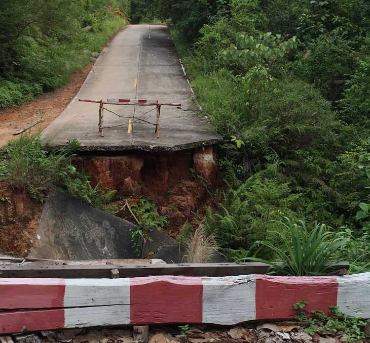 Broken bridge in Thailand with large road gap. Red and white traffic barriers warn drivers of the danger.