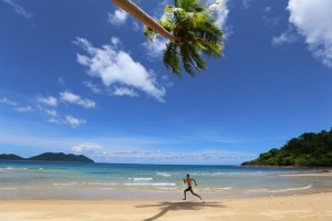 Man running on the beach under the shadow of a palm tree
