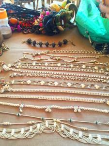 A display of anklets and bracelets spread out for sale on a table