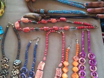Homemade necklaces in various colors on display on a table