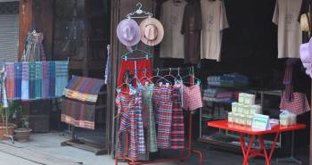 Charming tourist shop in Thailand displaying Thai products such as fisherman's pants, hats, and t-shirts.