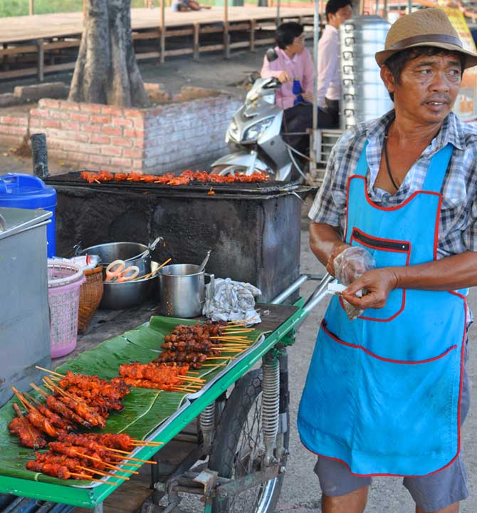 Thai street vendor selling chicken and beef satay.