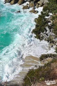 Powerful waves spilling in on beach on the rugged Pacific Westcoast at Big Sur in California