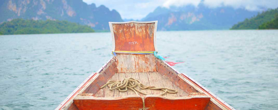Front view of a longtail boat in Thailand with limestone rocks in the background. Photo by Beachmeter.com.