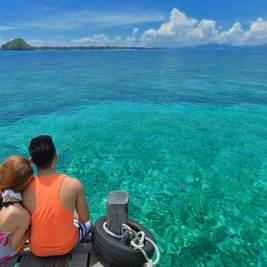 Malaysian couple sitting on a wooden pier looking at the clear turquoise sea and fantastic horizon.