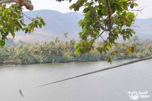 Girl ziplining over the Kampot River in Cambodia