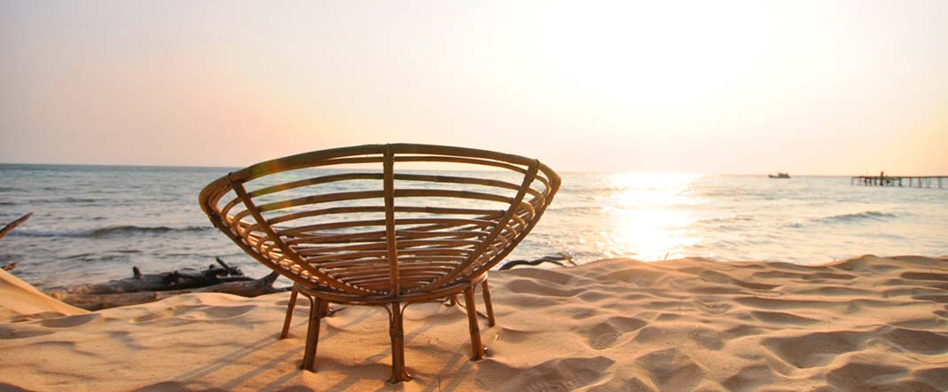 Cambodian sunset with Cambodian-style beach chair in the foreground. By Beachmeter.com.