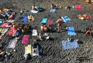 colorful beach towels on black sand beach