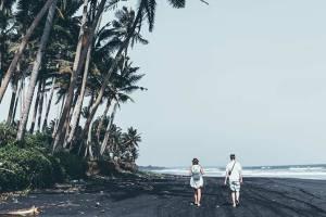 couple walking on black sand tropical beach