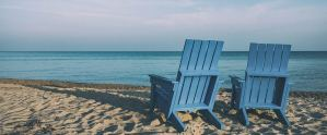 empty blue wooden chairs on beach