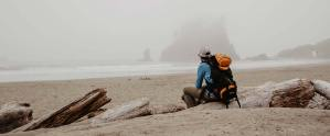Backpacker sitting on beach