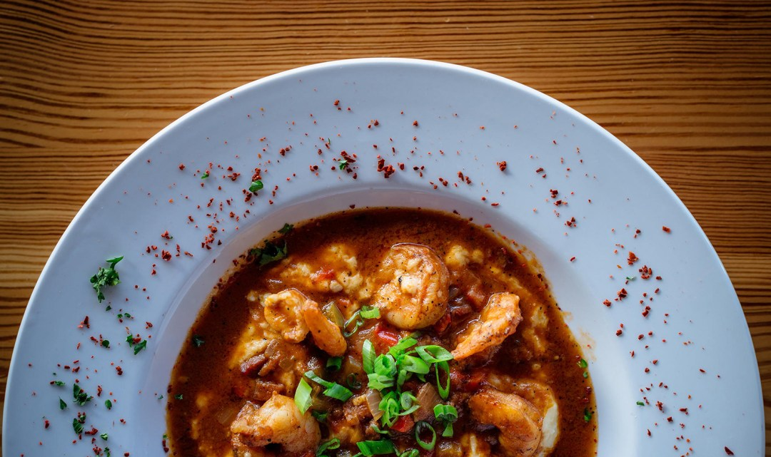 Shrimp and Grits: fresh, local shrimp with tasso ham, holy trinity creole broth, and white cheddar Anson Mills grits