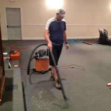 7/14/12 Pastor Bill vacuuming the wood shavings from the pulpit microphone holes he drilled