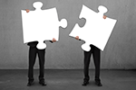 Two people holding large white puzzle pieces obscuring their faces.