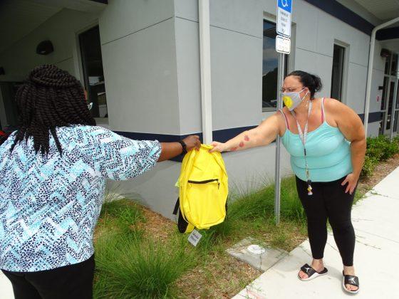 <p><p>Keeping six feet apart, Resource Center Administrator Shilretha Dixon hands off a backpack to parent Gandy Potestio.</p></p><p>BEACON PHOTO/MARSHA MCLAUGHLIN</p>